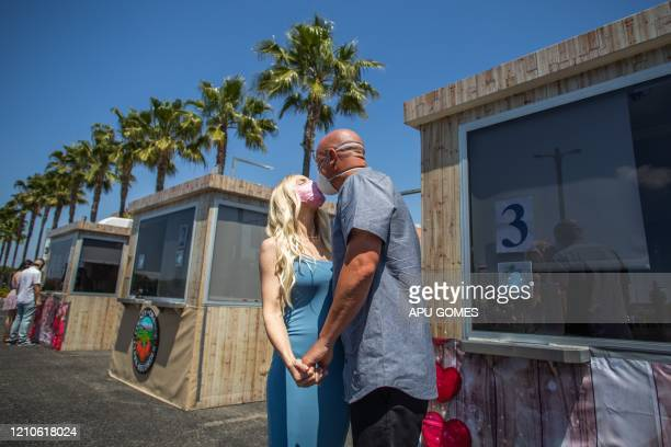 TOPSHOT Chad Robbins and Tracey Robbins kiss wearing face masks after their wedding ceremony officiated by a clerk recorder at the Honda Center...