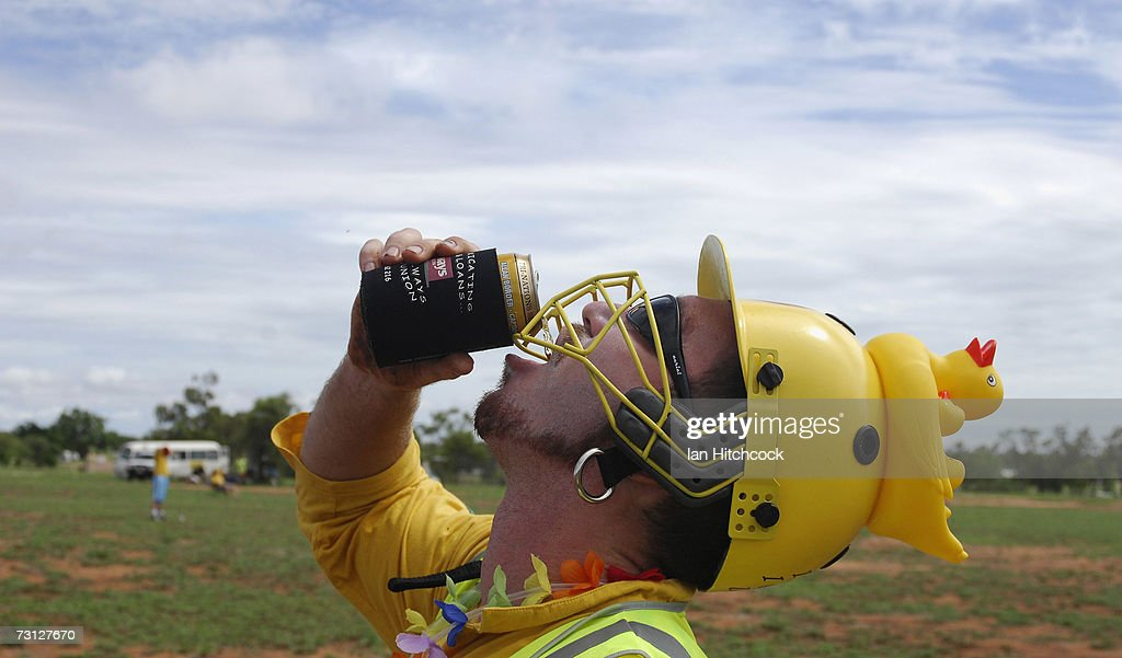 Chad Rosenblatt of the team 'Outcasts' wears a punishment helmet after he got out for a duck but is still able to drink a beer during the Goldfield Ashes January 27, 2007 in Charters Towers, Australia. Due to heavy overnight rain the three day cricket carnival was cancelled however several teams still came out and played. Every Australia Day weekend the small outback town of Charters Towers in North Queensland hosts a cricket carnival named 'The Goldfield Ashes'. In 1949 the Charters Towers Cricket Association extended an invitation to six town to play on Foundation Day. From those six teams the carnival has grown to a record 194 teams competing in 2007, making it the largest carnival of its type in the world. The Goldfield Ashes swells the 8000 strong population of Charters Towers, near Townsville, by about 3000 and attracts teams of solicitors, engineers and television crews from as far as Brisbane. Matches are played on 58 different playing fields, including some which are privately owned. It is one of the few sporting carnivals which caters for players of all levels of ability
