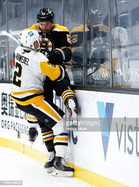 Chad Ruhwedel of the Pittsburgh Penguins checks Jeremy Lauzon of the Boston Bruins into the boards during the third period at TD Garden on January...