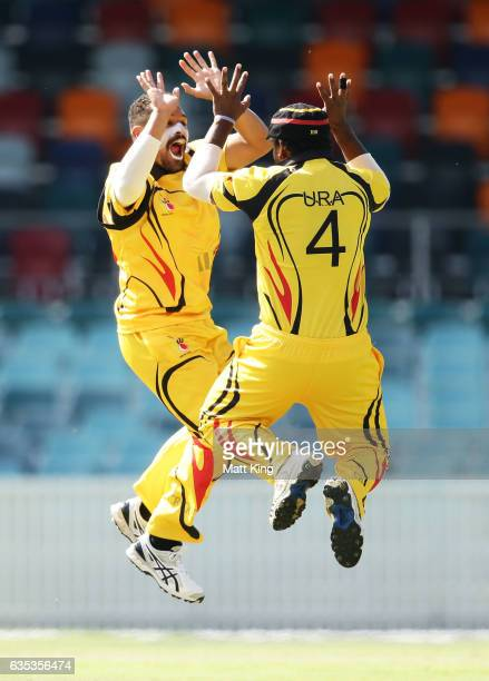 Chad Soper of Papua New Guinea celebrates with Tony Ura of Papua New Guinea after taking the wicket of Aiden Blizzard of ACT during the T20 warm up...
