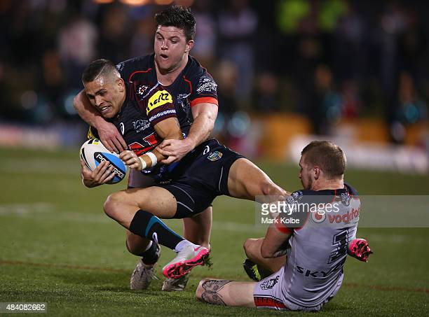 Chad Townsend and Sam Tomkins of the Warriors tackle Will Smith of the Panthers during the round 23 NRL match between the Penrith Panthers and the...