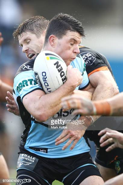 Chad Townsend of the Sharks is tackled by Chris Lawrence of the Tigers during the round 14 NRL match between the Cronulla Sharks and the Wests Tigers...