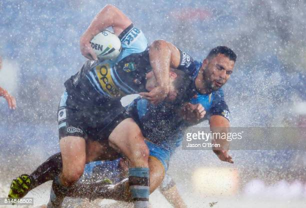 Chad Townsend of the sharks is tackled by Ryan James of the Titans during the round 19 NRL match between the Gold Coast Titans and the Cronulla...