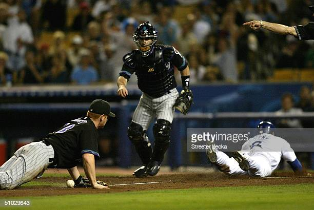 Chad Tracy of the Arizona Diamondbacks and teammate Robby Hammock can only watch as Olmedo Saenz of the Los Angeles Dodgers scores off a squeeze play...