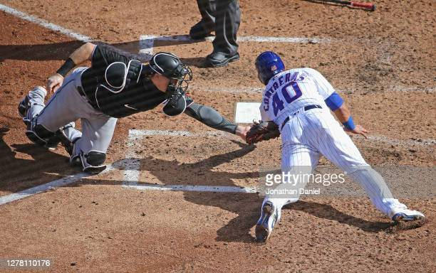 Chad Wallach of the Miami Marlins tags Willson Contreras of the Chicago Cubs out at the plate in the 4th inning during Game Two of the National...