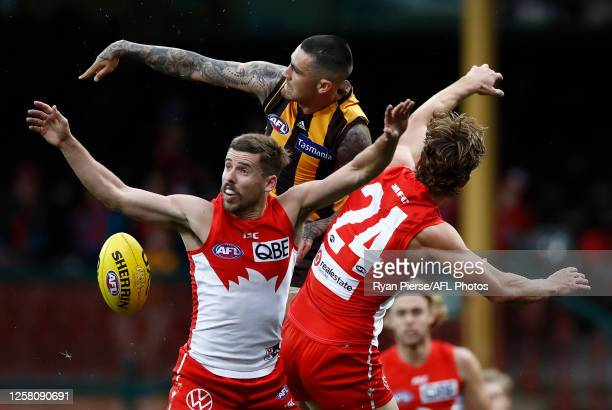 Chad Wingard of the Hawks is challenged by Jake Lloyd and Dane Rampe of the Sydney Swans during the round 8 AFL match between the Sydney Swans and...