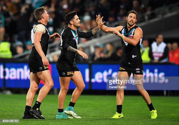 Chad Wingard of the Power celebrates with Brad Ebert and Travis Boak of the Power after kicking a goal during the round 23 AFL match between the Port...