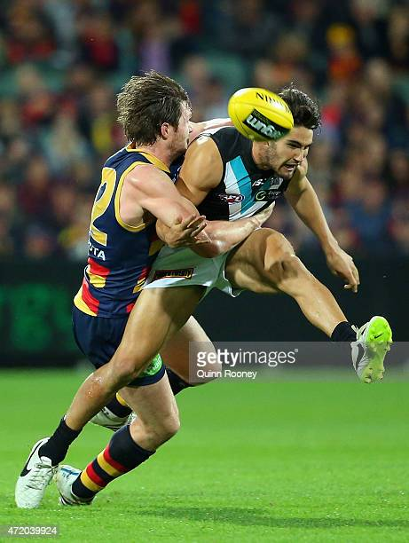 Chad Wingard of the Power kicks whilst being tackled by Patrick Dangerfield of the Crows during the round five AFL match between the Adelaide Crows...