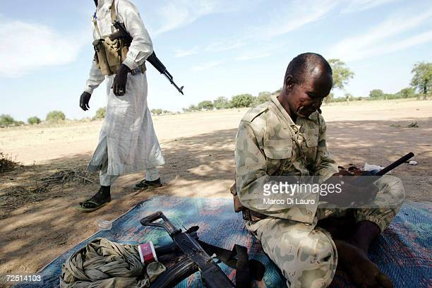 Chadian army soldier holds a Thuraya satellite phone during his assignment to protect village people and their children sheltering under trees after...