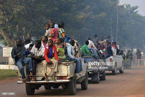 Chadian citizens sitting in the back of pick up trucks arrive at a camp set up near the airport in Bangui on December 29 2013 Desperate Chadian...