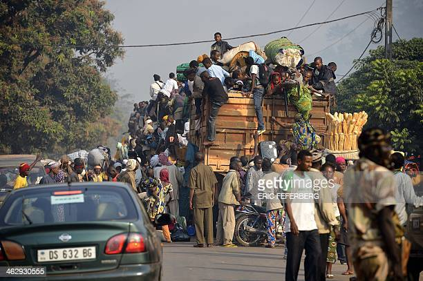 Chadian civilians climb on a military truck in the PK12 district of Bangui on January 16 2014 as they flee the Central African Republic and return to...