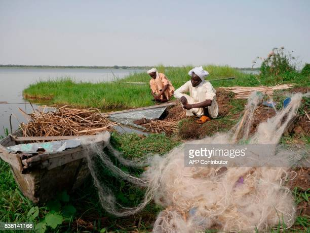 Chadian fishermen mend their nets on Midikouta Island on Lake Chad on July 22 2017 Tchoukouli one of hundreds of tiny interconnected islands about an...