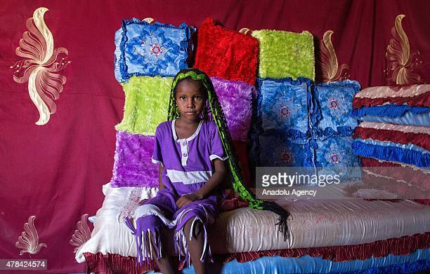 N'DJAMENA CHAD JUNE 22 A Chadian girl sits on a sofa with colorful pillows at a slumdog of N'djamena Chad on June 22 2015 Referred to as the 'Dead...