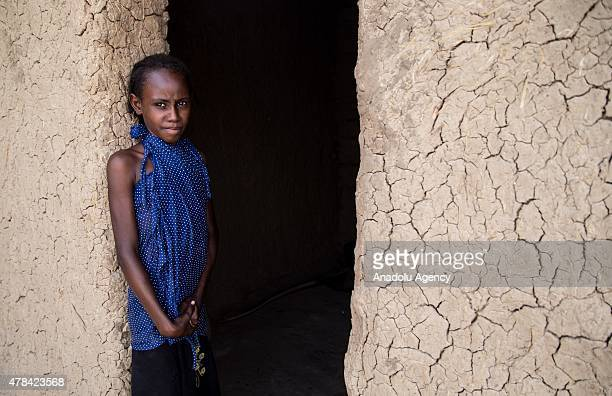 N'DJAMENA CHAD JUNE 22 A Chadian girl stands next to door of a house at a slumdog of N'djamena Chad on June 22 2015 Referred to as the 'Dead Heart of...