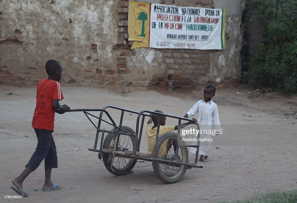 N'DJAMENA, CHAD - JUNE 22: A Chadian kid carries other kid with a wheelbarrow at a slumdog of N'djamena, Chad on June 22, 2015. Referred to as the 'Dead Heart of Africa', the majority of Chads population does not respect the rights of children. One of the main problems faced by children is poverty. Chad, a crossing point between sub-Saharan Africa and North Africa, is one of the poorest countries in the world. Thus, poverty, which affects a vast majority of young Chadians, has serious repercussions on their access to a healthy diet, adequate financial resources, healthcare, etc. Also, in Chad, the mortality rate of children under five is very worrisome. In fact, due to the lack of sanitation, drinking water and healthcare in rural areas, 209 children out of 1000 die every year. Another problem is education. The population of Chad is so disparate that Childrens Rights to education are compromised. In addition, parents are often reluctant to send their children to school. Only a small percentage of children in Chad are schooled. Crucial problem is child marriages. The marriage of young girls is still a common practice in Chad, as the age of majority is set differently within various documents. From a legal point of view, civil majority is reached at 21 years and the legal age of marriage is set at 15 years for girls and 18 years for boys. However in customary law, the age of marriage is implicitly set at 13 years, which goes against the International Convention on the Rights of the Child. Other issue is child labor. In Chad, the minimum age for employment is 14 years. However, due to economic difficulties, many families are often forced to make their children work.