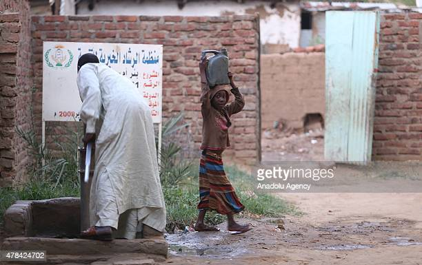 N'DJAMENA CHAD JUNE 22 A Chadian kid carries water with a jelly jar on the top of her head at a slumdog of N'djamena Chad on June 22 2015 Referred to...