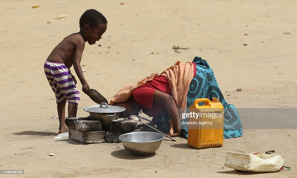 N'DJAMENA, CHAD - JUNE 22: A Chadian kid helps his mother to light a fire at a slumdog of N'djamena, Chad on June 22, 2015. Referred to as the 'Dead Heart of Africa', the majority of Chads population does not respect the rights of children. One of the main problems faced by children is poverty. Chad, a crossing point between sub-Saharan Africa and North Africa, is one of the poorest countries in the world. Thus, poverty, which affects a vast majority of young Chadians, has serious repercussions on their access to a healthy diet, adequate financial resources, healthcare, etc. Also, in Chad, the mortality rate of children under five is very worrisome. In fact, due to the lack of sanitation, drinking water and healthcare in rural areas, 209 children out of 1000 die every year. Another problem is education. The population of Chad is so disparate that Childrens Rights to education are compromised. In addition, parents are often reluctant to send their children to school. Only a small percentage of children in Chad are schooled. Crucial problem is child marriages. The marriage of young girls is still a common practice in Chad, as the age of majority is set differently within various documents. From a legal point of view, civil majority is reached at 21 years and the legal age of marriage is set at 15 years for girls and 18 years for boys. However in customary law, the age of marriage is implicitly set at 13 years, which goes against the International Convention on the Rights of the Child. Other issue is child labor. In Chad, the minimum age for employment is 14 years. However, due to economic difficulties, many families are often forced to make their children work.