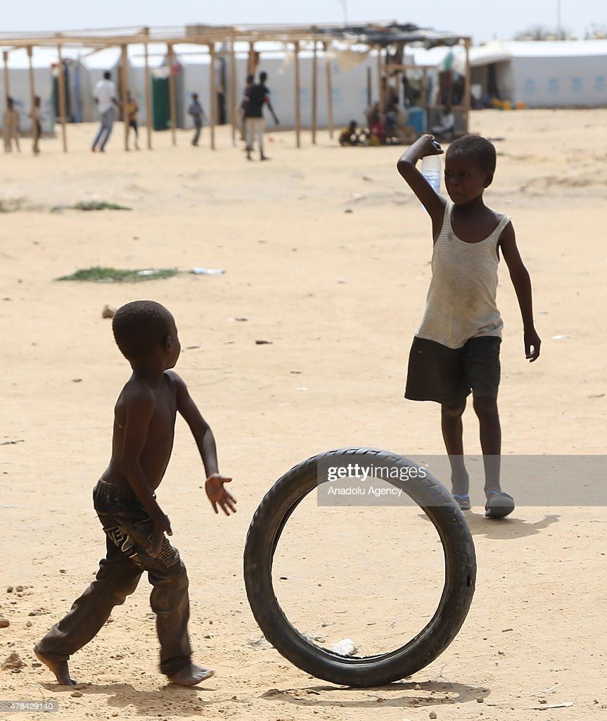 N'DJAMENA, CHAD - JUNE 22: A Chadian kid plays with a tire as other holds a bottle of water at a slumdog of N'djamena, Chad on June 22, 2015. Referred to as the 'Dead Heart of Africa', the majority of Chads population does not respect the rights of children. One of the main problems faced by children is poverty. Chad, a crossing point between sub-Saharan Africa and North Africa, is one of the poorest countries in the world. Thus, poverty, which affects a vast majority of young Chadians, has serious repercussions on their access to a healthy diet, adequate financial resources, healthcare, etc. Also, in Chad, the mortality rate of children under five is very worrisome. In fact, due to the lack of sanitation, drinking water and healthcare in rural areas, 209 children out of 1000 die every year. Another problem is education. The population of Chad is so disparate that Childrens Rights to education are compromised. In addition, parents are often reluctant to send their children to school. Only a small percentage of children in Chad are schooled. Crucial problem is child marriages. The marriage of young girls is still a common practice in Chad, as the age of majority is set differently within various documents. From a legal point of view, civil majority is reached at 21 years and the legal age of marriage is set at 15 years for girls and 18 years for boys. However in customary law, the age of marriage is implicitly set at 13 years, which goes against the International Convention on the Rights of the Child. Other issue is child labor. In Chad, the minimum age for employment is 14 years. However, due to economic difficulties, many families are often forced to make their children work.