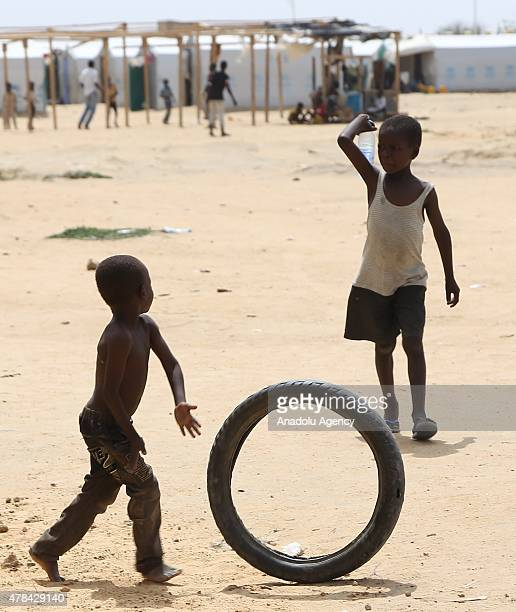 N'DJAMENA CHAD JUNE 22 A Chadian kid plays with a tire as other holds a bottle of water at a slumdog of N'djamena Chad on June 22 2015 Referred to as...