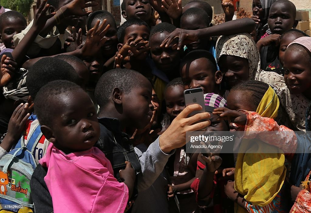 N'DJAMENA, CHAD - JUNE 22: Chadian kids pose for a selfie with a man at a slumdog of N'djamena, Chad on June 22, 2015. Referred to as the 'Dead Heart of Africa', the majority of Chads population does not respect the rights of children. One of the main problems faced by children is poverty. Chad, a crossing point between sub-Saharan Africa and North Africa, is one of the poorest countries in the world. Thus, poverty, which affects a vast majority of young Chadians, has serious repercussions on their access to a healthy diet, adequate financial resources, healthcare, etc. Also, in Chad, the mortality rate of children under five is very worrisome. In fact, due to the lack of sanitation, drinking water and healthcare in rural areas, 209 children out of 1000 die every year. Another problem is education. The population of Chad is so disparate that Childrens Rights to education are compromised. In addition, parents are often reluctant to send their children to school. Only a small percentage of children in Chad are schooled. Crucial problem is child marriages. The marriage of young girls is still a common practice in Chad, as the age of majority is set differently within various documents. From a legal point of view, civil majority is reached at 21 years and the legal age of marriage is set at 15 years for girls and 18 years for boys. However in customary law, the age of marriage is implicitly set at 13 years, which goes against the International Convention on the Rights of the Child. Other issue is child labor. In Chad, the minimum age for employment is 14 years. However, due to economic difficulties, many families are often forced to make their children work.