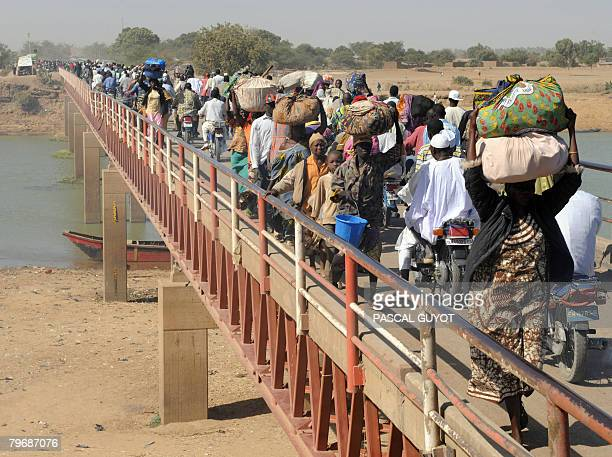 Chadian refugees and residents cross on February 10 2008 the Ngueli bridge at the border between Cameroon and Chad to return to their homes in the...