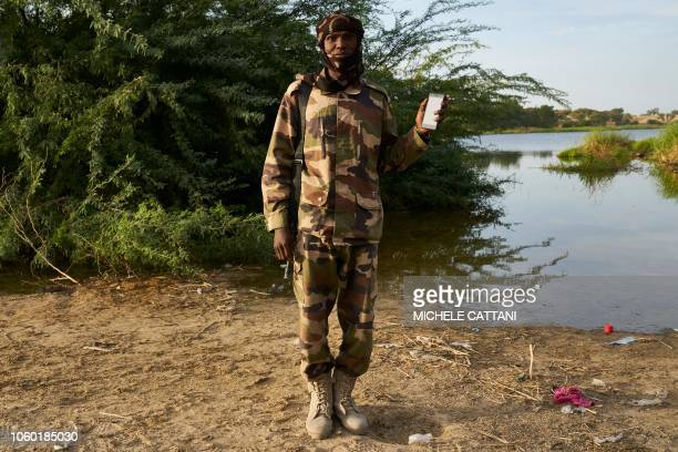 Chadian soldier Ali Adam Agar poses with a smartphone in front of Lake Chad on November 7 2018 Ali uses his smartphone to listen the Quran's verses...
