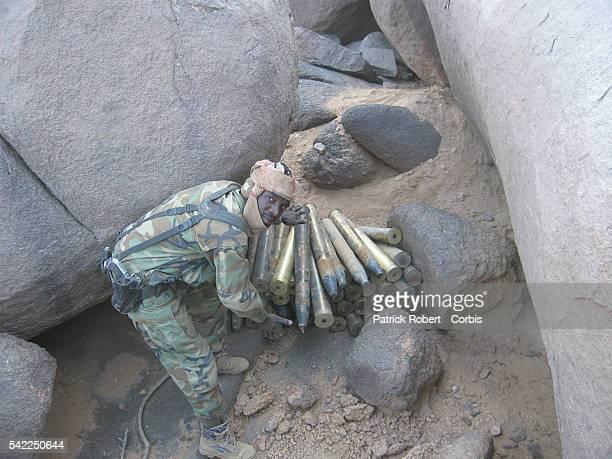 A Chadian soldier displays a weapon cache of Islamist Djihadists in the Malian desert