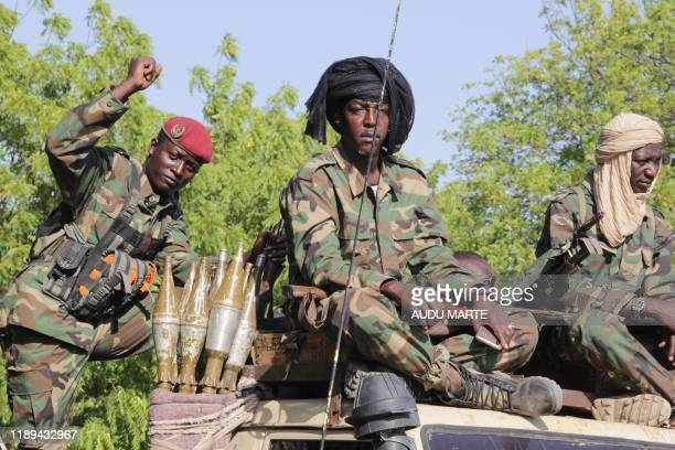Chadian soldiers belonging to the Joint Task Force gesture while patrolling in Monguno on December 15, 2019. - Fourteen people were killed and 13...