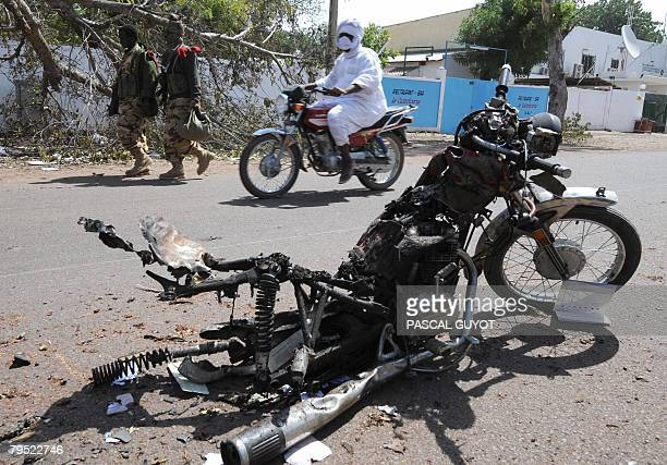 Chadian soldiers walk past the burntout wreck of a motorbike in the capital city N'Djamena on February 05 2008 after violent fighting Rebels in Chad...