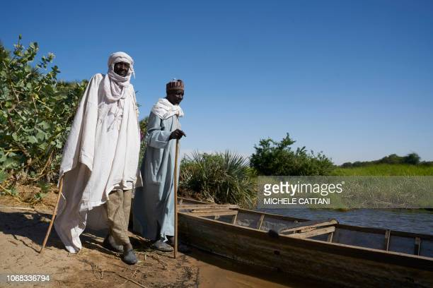 Chadian stand near a wooden boat on the shores of Lake Chad on November 8 2018