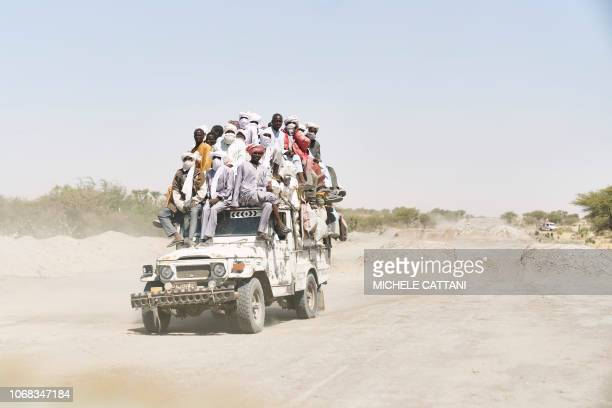 TOPSHOT Chadian travels on a overloaded truck across the desert on the way to Bol in southern Chad on November 9 2018 These old and overcharged...