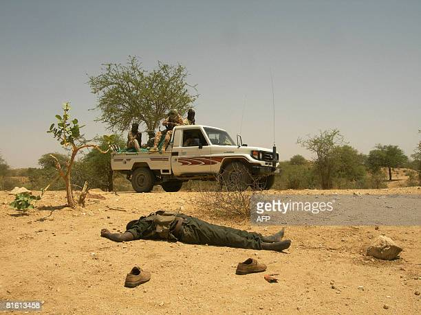 Chadian troops in a pickup drive past a dead rebel soldier after having routed rebel forces in Am Zoer north east of the capital Abeche on June 18...