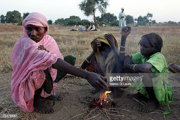 Chadian village women lights a fire watched by her children whilst sheltering under trees after fleeing an attack on their village on November 9 2006...