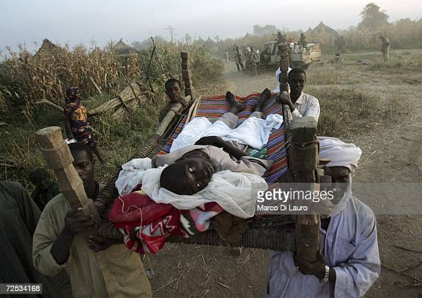Chadian villagers carry a wounded man during a Chadian Army rescue mission on November 13 2006 in Bandikao Village 90 Km south of Goz Beida Chad...