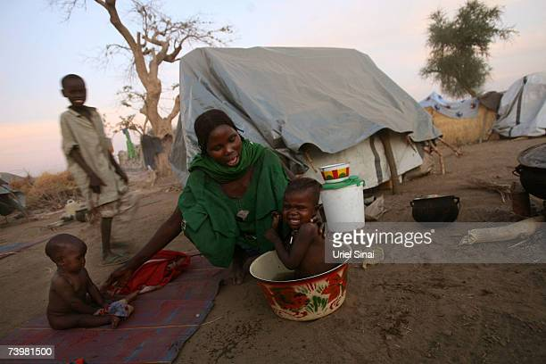A Chadian woman washes her baby as the sun goes down over Habile IDP Camp near the border with Sudan April 2007 in Chad Tensions between Chad and...
