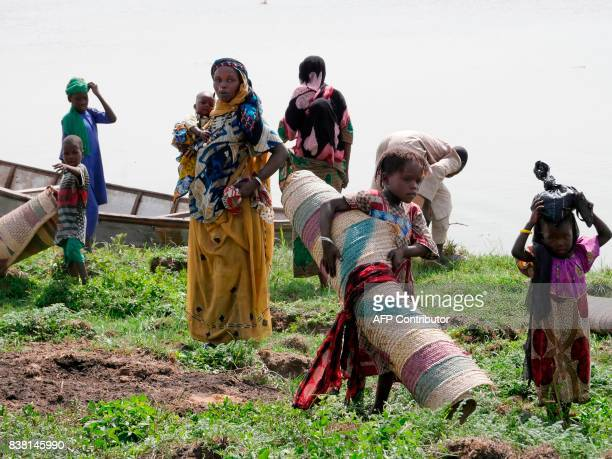 Chadian women carry carpets and few other belongings as they travel back on Midikouta Island on Lake Chad on July 22 2017 Tchoukouli one of hundreds...