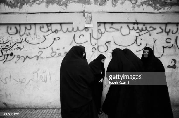 Chador clad women stand in front of a mural with revolutionary slogans in Shah Reza avenue in Tehran during one of the most important days of the...