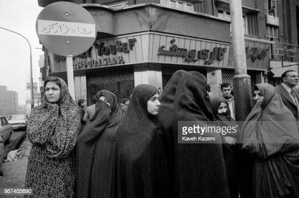 Chador clad women stand in front of a Shah Ran slogan sprayed on a no entry street sign in Shah Reza avenue a few days after the Shah fled the...