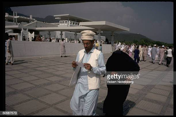 Chadorclad Moslem woman modestly shrinking fr camera covering face walking w man prob leaving Faisal Mosque