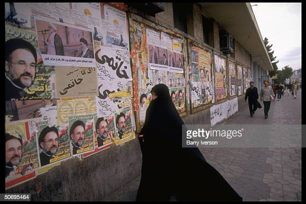 Chador-clad woman by wall plastered w. Presidential election campaign posters mostly picturing moderate cleric Mohammed Khatami, surprise...