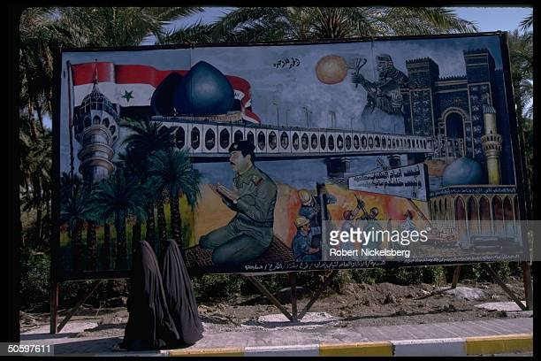 Chadorclad women passing mural depicting Pres Saddam Hussein in mil uniform praying framed by Saddam Tower bridge mosque Martyr's Monument