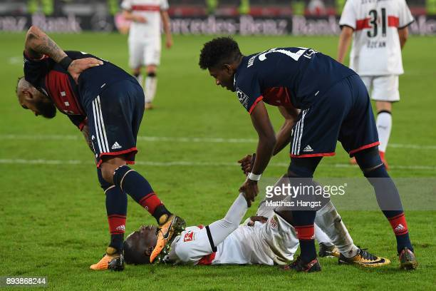 Chadrac Akolo of Stuttgart lies on the pitch after he missed a penalty as David Alaba of Bayern Muenchen and Arturo Vidal of Bayern Muenchen look...