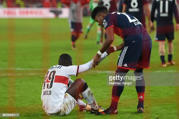 Chadrac Akolo of Stuttgart sits on the pitch after he missed a penalty as David Alaba of Bayern Muenchen looks after him during the Bundesliga match...
