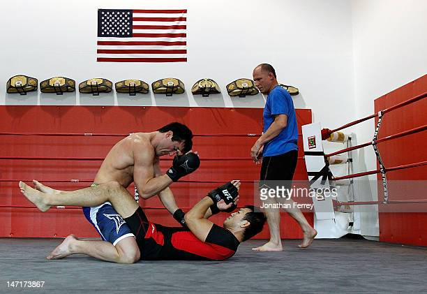 Chael Sonnen grapples with Yushin Okami as his coach Scott McQuary watches during a workout at the Team Quest gym on June 26 2012 in Tualatin Oregon...