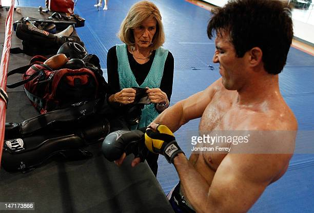 Chael Sonnen puts on his gloves with the help of his mother Claudia during a workout at the Team Quest gym on June 26 2012 in Tualatin Oregon Sonnen...