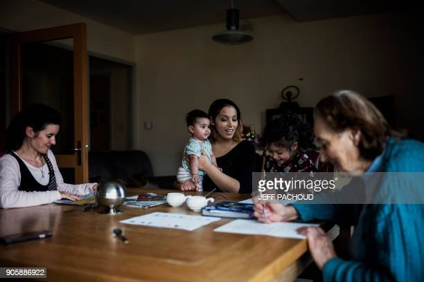 TOPSHOT Chahad Khadiri who started to host people at her home two and a half years ago plays with her children next to an elderly woman and a...