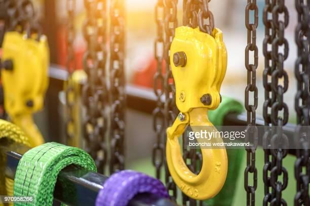 chain and yellow hoist on background - 吊り上げる ストックフォトと画像