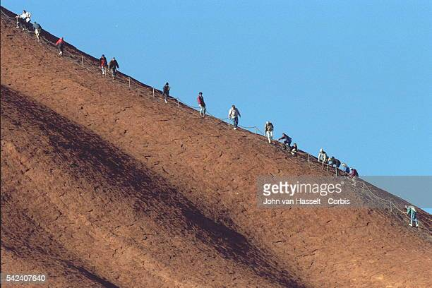 Chain has been built to make the climb easier for the thousands of people who come from all overthe world to scale the heights of the Uluru mono-...