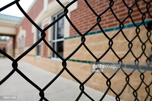Chain link fence and school building. Education. Nobody.