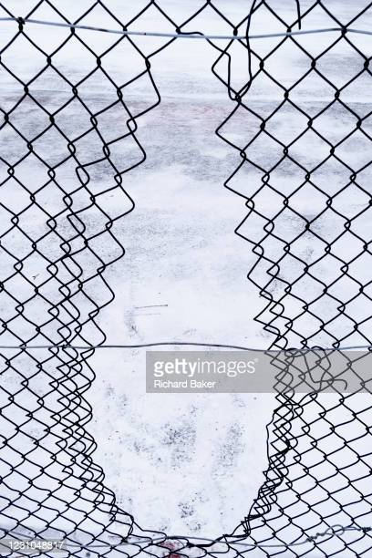 Chain link fence has been cut to allow younger park-users entry through its aperture and into a snow-covered basketball court area in Ruskin Park, on...